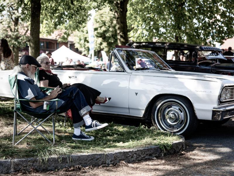 Älteres Paar sitzend vor ihrem Oldtimer